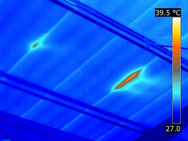 Zwei undichte Stoßfugen entlang von Sandwich-Deckenelementen während hochsommerlicher Witterung im Unterdruckbetrieb
