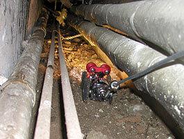 Inspektion eines Leitungsschachts. Hier mit einem Fahrwagen, der mit einer Schwenkkopfkamera ausgestattet ist.